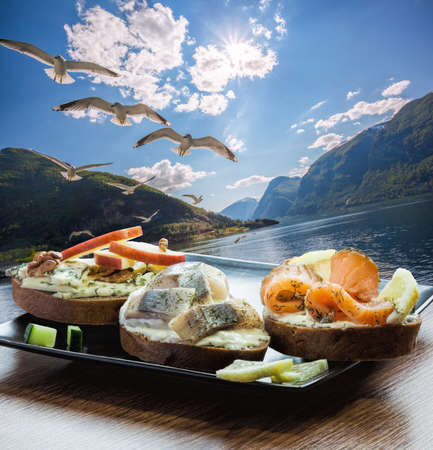 Typical Scandinavian sandwiches against fjord with seagulls near the Flam village in Norway