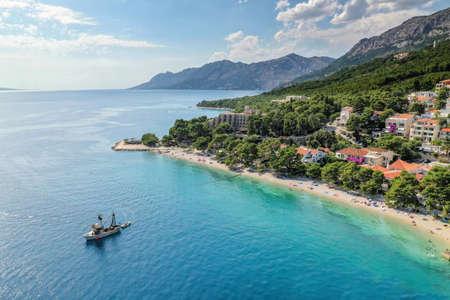 Aerial view of Brela with beach and fishing boat in Dalmatia, Croatia