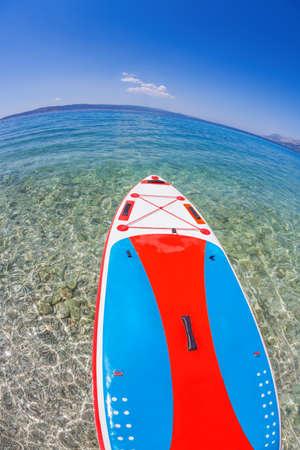 Colorful paddle board against azure sea in Brela, Croatia