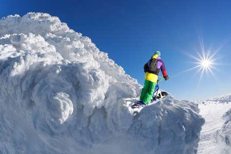 Skier on monoski in high mountains against blue sky Фото со стока