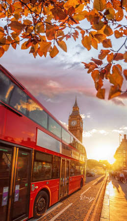 Big Ben against colorful sunset with red bus during autumn in London, England