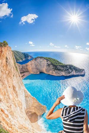 Woman with hat watching Navagio beach with shipwreck on Zakynthos island in Greece Фото со стока