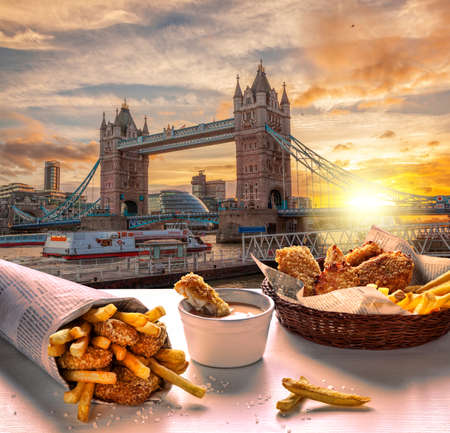 Tower Bridge against fish and chips served on the table in London, United Kingdom