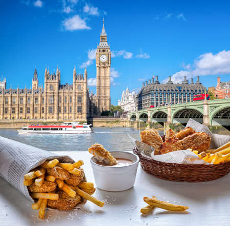 Big Ben against fish and chips served on the table in London, United Kingdom
