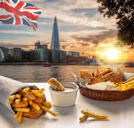 Downtown of London against fish and chips served on the table in England, United Kingdom
