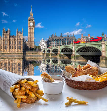 Big Ben against fish and chips served on the table in London, England, United Kingdom Фото со стока