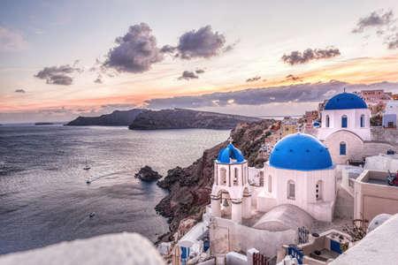 Oia village with churches against sunset on Santorini island in Greece Фото со стока
