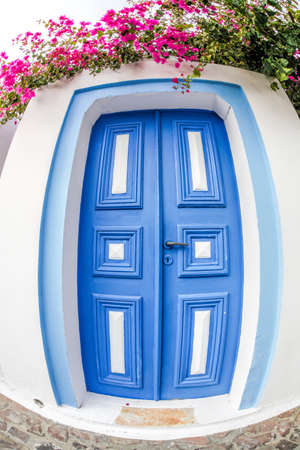 Oia village with typical old blue door on Santorini island in Greece Фото со стока