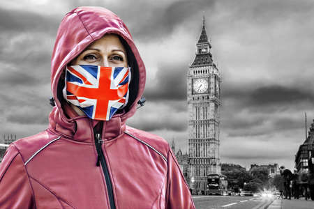 Woman wearing protection face mask with British flag against coronavirus in front of the Big Ben, London, England
