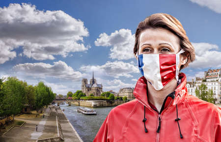 Woman wearing protection face mask with French flag against coronavirus near the Notre Dame cathedral with sunrise in France