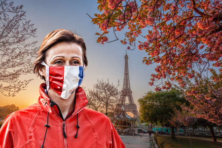 Woman wearing protection face mask with French flag against coronavirus in front of the Eiffel Tower in Paris, France Фото со стока