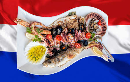 Amazing seafood plate with fish, scallops, prawns, octopus served on Croatian flag