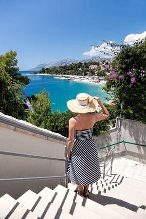 Beautiful woman watching amazing Croatian beaches in Brela, Dalmatia, Croatia
