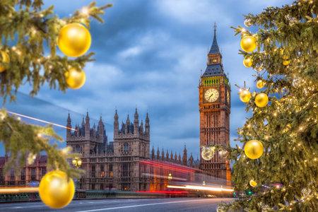 Big Ben with Christmas tree on bridge at night in London, England, United Kingdom Фото со стока