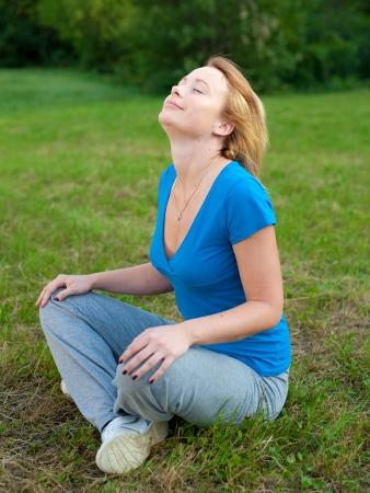 Cute girl meditates in nature photo