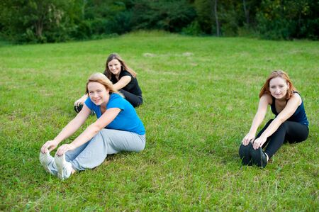 Three girls exercise in park photo