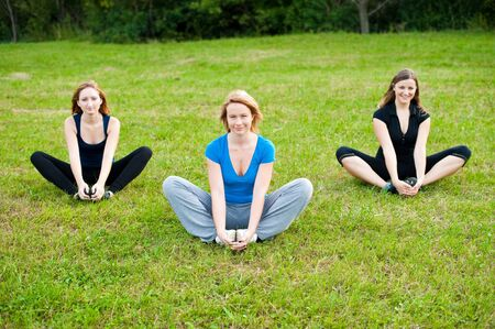 Group of young girls work out on a grass field