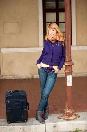 Cute young girl in purple jacket and jeans on railway station photo