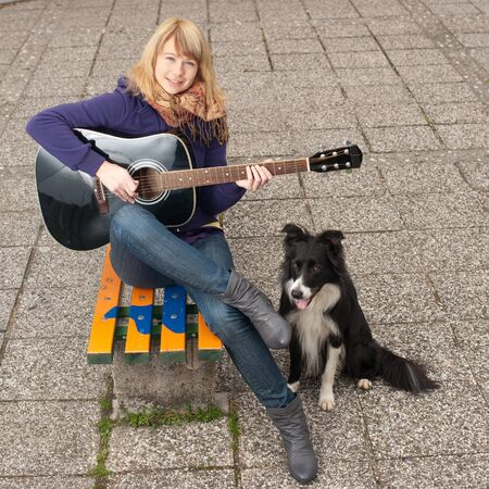 cute young girl with guitar and puppy photo