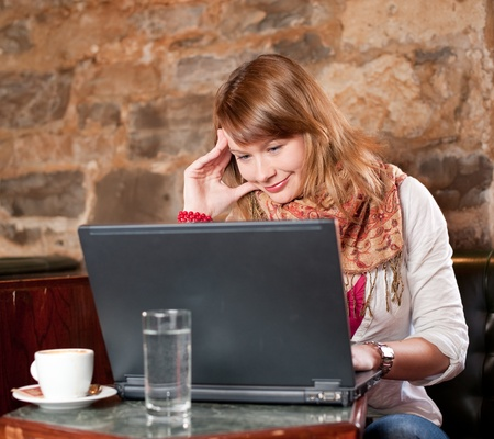 Morning coffee in internet cafe - Beautiful young girl checking news on web and drinking coffe photo
