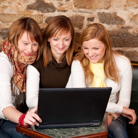 chat online: Three beautiful young students waiting for coffee and checking news on laptop