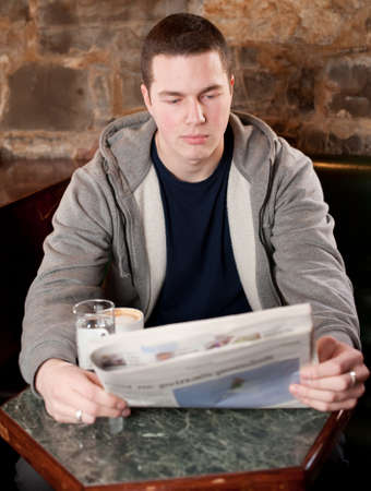 Morning coffee and news - Handsome young man reading newspaper in a bae and drinking coffee photo