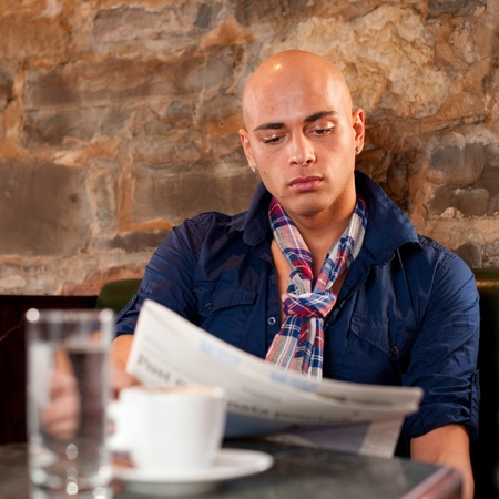 Morning coffee and news - Handsome young man reading newspaper in a bae and drinking coffee