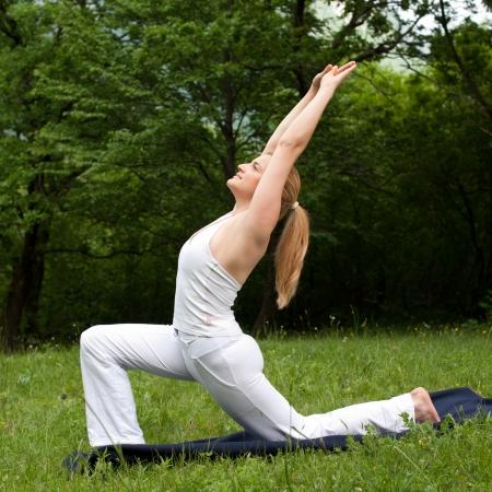 Meditation in der Natur - hübsch junges Mädchen meditiert im freien auf einem grünen Rasen im park