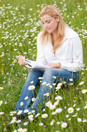 Beautiful young woman reading a book outdoors on a grass field in park Stock Photo - 9599491