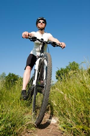 Jong meisje een fiets rijden op een veld pad - offroad