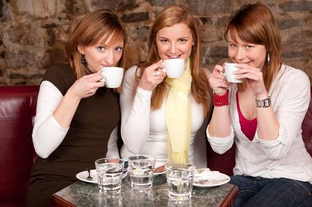 Three beautiful young students waiting drinking  coffee and having a debate in coffee shop photo