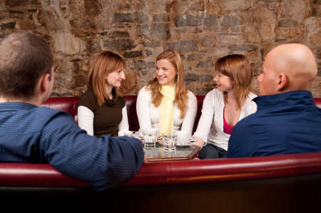 Group of five people having fun in cafe photo