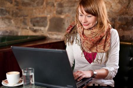 Mañana café en café internet - hermosa joven comprobación de noticias en la web y beber café Foto de archivo
