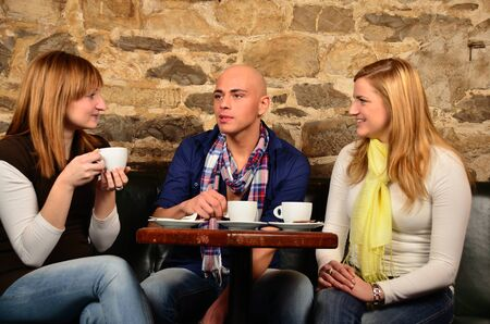 Three friends in cafe discussing and having fun photo