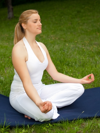 Meditation in nature - Cute young girl meditates outdoor on a green grass field in park photo