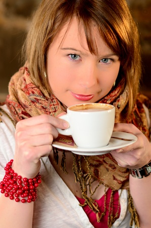 Beautiful young girl dtinking coffee photo