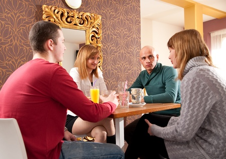 just arrived: Man just arrived in a caffee where three girls were expecting him Stock Photo