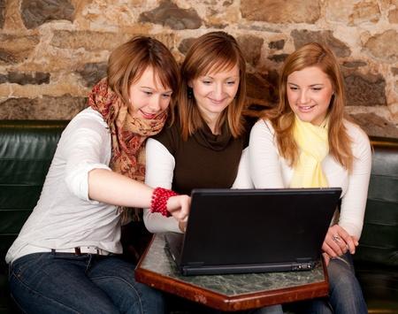 Drie mooie jonge studenten te wachten op koffie en het controleren van nieuws op laptop