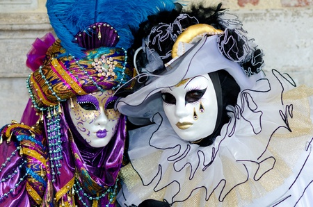 VENECIA, Italia - 07 de marzo: Una pareja de enmascarados no identificados posar delante de la iglesia de San Marcos en Venecia, durante el carnaval anual de Venecia. El carnaval es de febrero 26 a marzo 8, 2011.