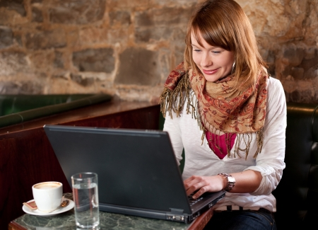 Morning coffee in internet cafe - Beautiful young girl checking news on web and drinking coffe Foto de archivo