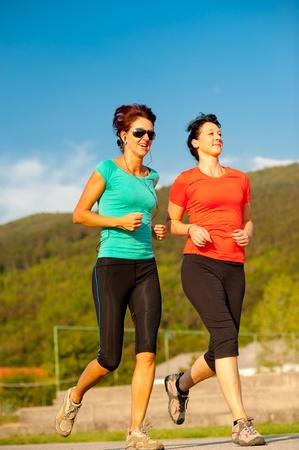 mujeres corriendo: Dos mujeres j�venes de correr al aire libre Foto de archivo