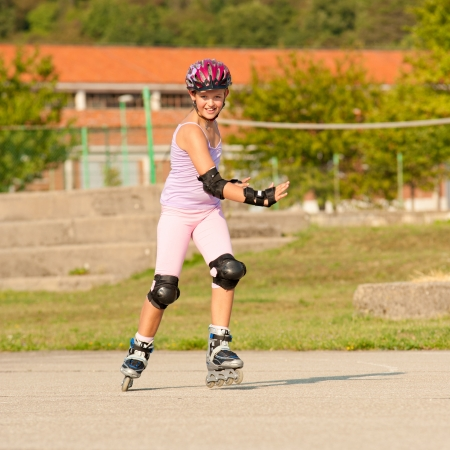 Cute young girl rollerskates on a playground Stock Photo