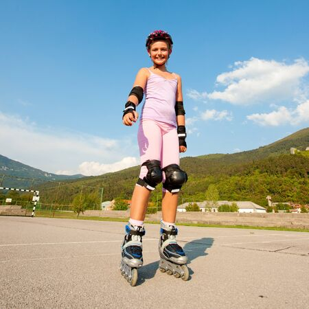 Cute young girl rollerskates on a playground Stock Photo - 11224312