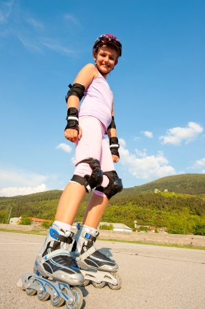 Cute young girl rollerskates on a playground Standard-Bild