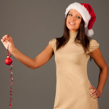 Attractive  girl in Santa Hat  and golden dressisolated on gray background photo