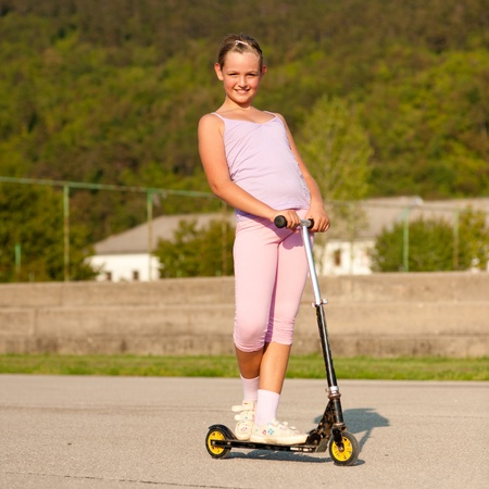 Cute teenage girl in pink dress on scooter photo