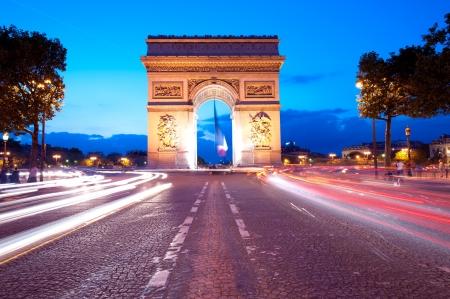 La noche el tráfico en los Campos Elíseos frente a Arco del Triunfo (París, Francia)