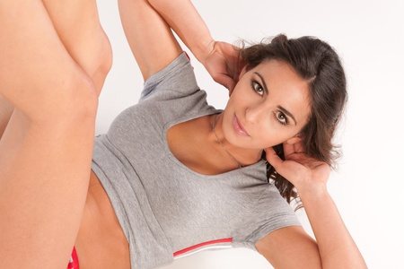 situps: Beautiful active young woman doing situps over white background