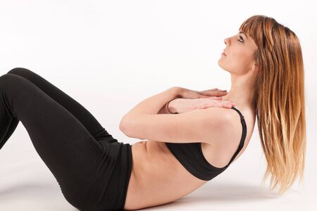 Beautiful active young woman doing situps over white background photo