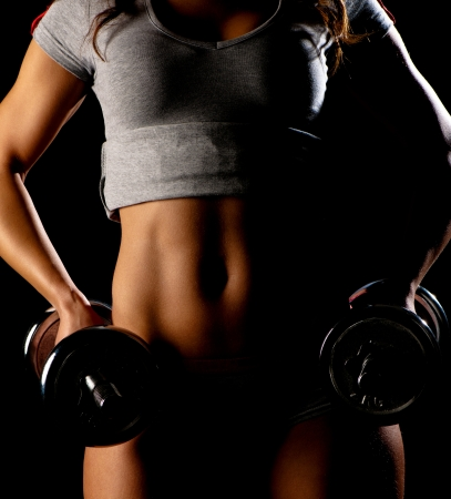 Young fit girl working out with weights - Portrait of pretty young woman lifting dumbbells during exercising Stock Photo - 12153068